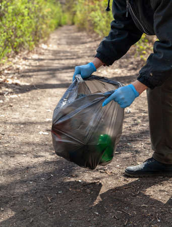 We save nature from garbage. Ecologist in blue rubber gloves collects trash in a black plastic bag in the forest Reklamní fotografie - 156564594
