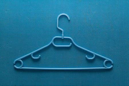 Plastic clothes hanger lies on a blue background in a small cage