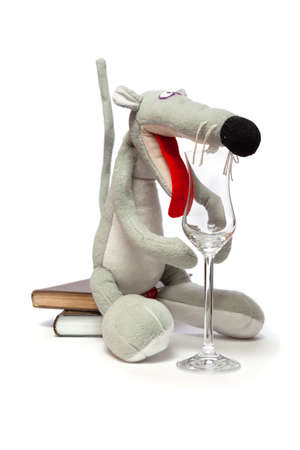 Rat and a glass. Symbol of 2020. Cute gray rat sits on a stack of books on a white background close-up. In front of her is an elegant glass goblet on a long leg. Reklamní fotografie - 156782612