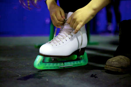 Hands tie a long lace on a white leather shoe of a modern skate with a green cover. Close-up Reklamní fotografie