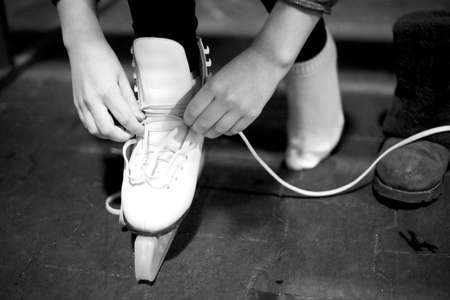 Hands tie a long lace on a white leather shoe of a modern skate. Monochrome image Reklamní fotografie - 156783805