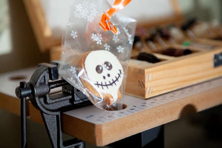 Halloween in the workshop. Halloween biscuits in a transparent package stand next to a vise in a tool shop