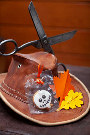 Merry Halloween. Round Halloween biscuits in a package lie on a leather hat. Nearby lie the paper leaves of oak and maple. Top vintage scissors