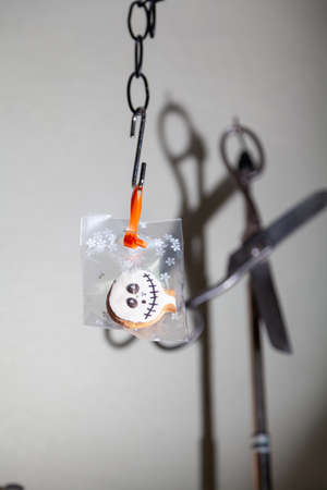 transparent Halloween cookies weigh on a steel hook. Vintage scissors hanging on the back of the counter