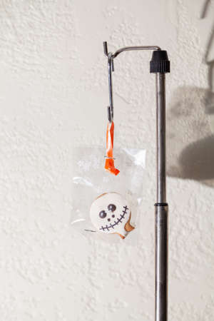 Halloween cookies in transparent packaging weigh on a steel rack against a white wall background