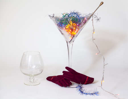 huge glass martini goblet stands on a white background. A magic cocktail shines in it. From below the glass is hugged by empty red gloves. There is a large cognac glass nearby Reklamní fotografie