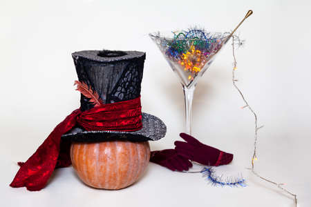 Halloween set. A large top hat on a ripe pumpkin and a magic cocktail in a huge glass martini glass. Bottom pair of red gloves Reklamní fotografie