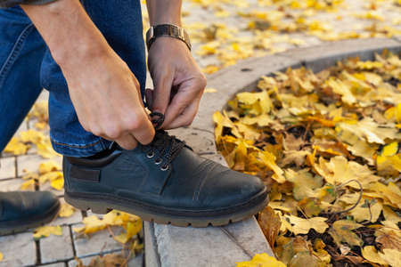 man in blue jeans tying shoelace in autumn city park close-up 免版税图像