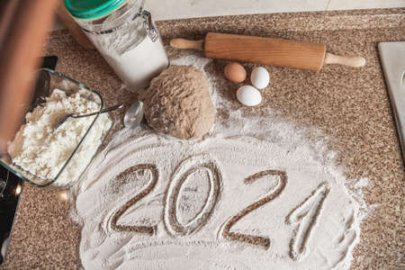 New Year in the kitchen. 2021 is written in flour. A piece of dough, eggs and a wooden rolling pin lies on a granite countertop.