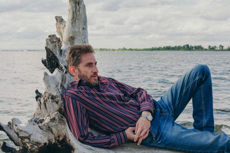 bearded man with a pensive look lies on an old driftwood log by the river