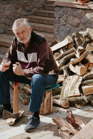 Portrait of an elderly man with a beard. A nice senior citizen is sitting in front of a pile of firewood. He holds an ax in his left hand. In his right hand holds a glass of whiskey