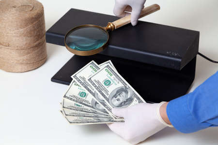 Hands in rubber gloves verify the authenticity of dollar bills with a detector. Nearby lies a large magnifier