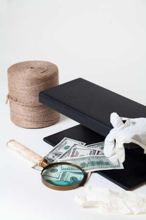 Verification of dollar bills using a close-up UV detector. Nearby lies a magnifying glass and rubber gloves. Worth a roll of rope