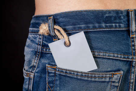 gray cardboard label sticks out in the back pocket of a trendy blue jeans close-up. Top body