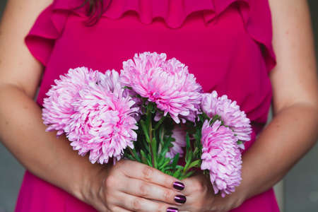 girl in a red dress holding a bouquet of pink chrysanthemums