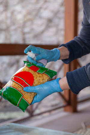 Prevention of infection at home. Hands in blue rubber gloves spray an aerosol antiseptic on the products in the package. Close-up.