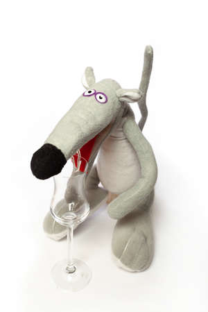 Rat and a glass. Symbol of 2020. Cute gray rat stands on a white background close-up. In front of her is an elegant glass goblet on a long leg