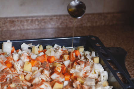 Stream of yellow vegetable oil pouring from a tablespoon into a baking sheet with chopped vegetables