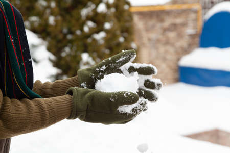 Winter fun. Hands in green fleece gloves form snowballs on a frosty day close-up 写真素材
