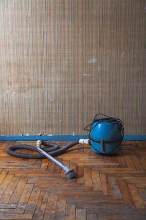 antique vacuum cleaner with a long hose stands on a scratched parquet floor in front of a wall 写真素材