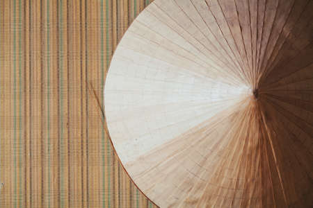 Asian conical hat made of palm leaves weighs right on the wall with vertical stripes on wallpaper 写真素材