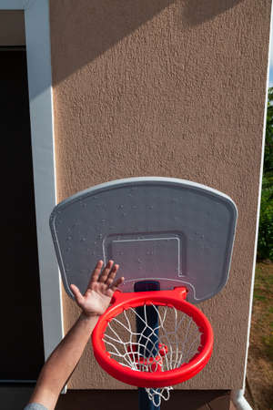 Hands on plastic basketball basket for playing at home. Quarantine entertainment for adults and children 写真素材