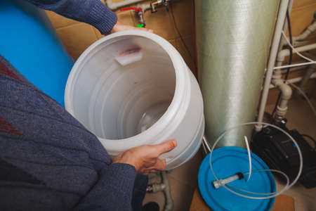 Plumber's hands hold round plastic osmosis water treatment system water tank 写真素材