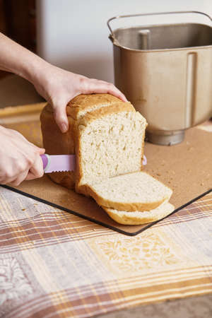 woman hands are cut with a large lilac knife with the teeth of a loaf of bread close-up 写真素材