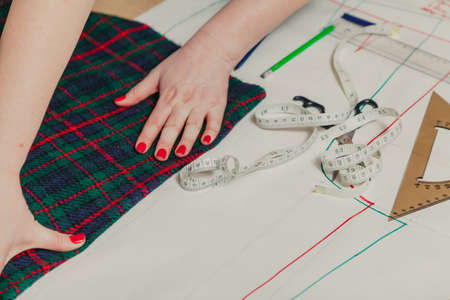 Designer creates a model. Female hands with a manicure make markings on a piece of Scottish fabric