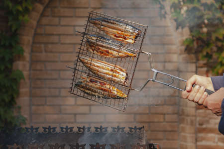 Cooking fish on the grill. Hands turn over metal grill with fish