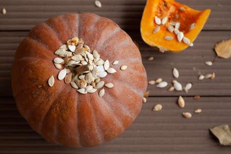 Autumn still life. A large round pumpkin and fallen leaves of trees lie on the boards. Top white seeds