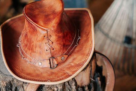 Cowboy headdress. Leather hat lie on a tree stump.