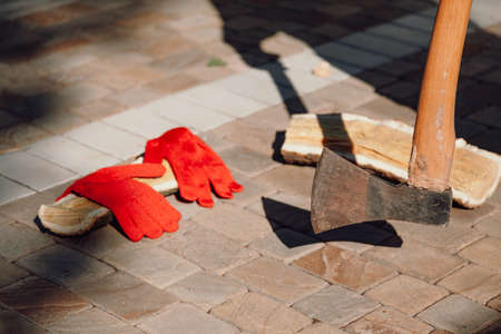 ax casts a shadow on the paving slabs in the yard. Nearby lies a chopped log and red work gloves