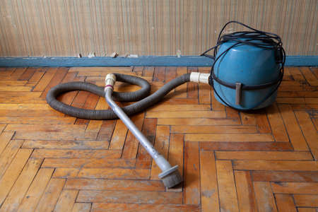 antique vacuum cleaner with a long hose stands on a scratched parquet floor in front of a wall 免版税图像