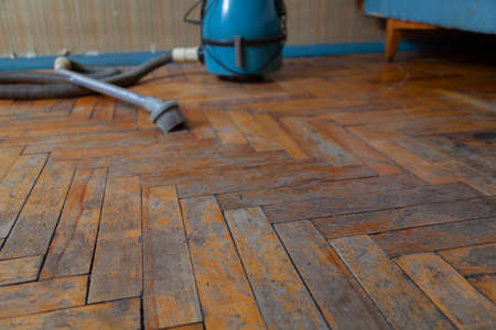 Old parquet floor close up. Paint and varnish are peeling off the wooden planks. There is a blue vacuum cleaner in the background 免版税图像