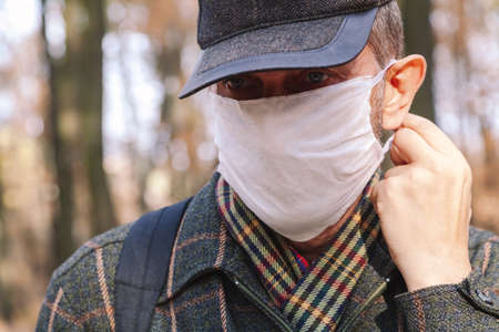 man in a cap puts on a white medical mask in the autumn forest