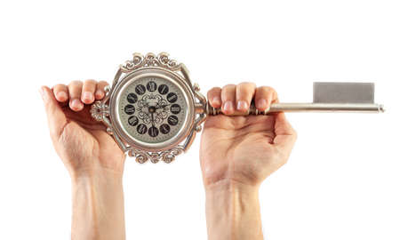Round clock in the form of a souvenir key in hands on a white background Zdjęcie Seryjne