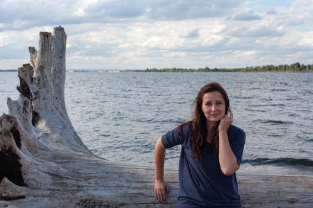 Young curve woman resting on an old big log on the river bank on a summer day