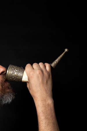 man with a beard holds the horn for wine with his right hand and drinks from it. Profile view Zdjęcie Seryjne