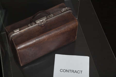 Business attributes. Close-up of a contract printed on paper and a leather carpetbag in a transparent box. The pen is on top of the contract