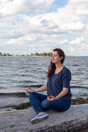 Young plump woman sits on a log by the river in a lotus position. Meditation and oneness with nature Zdjęcie Seryjne