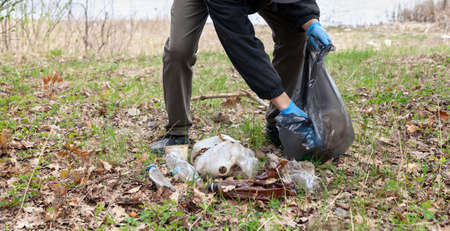 We save nature from garbage. A man in blue rubber gloves collects plastic garbage in a black bag on the shore of a pond