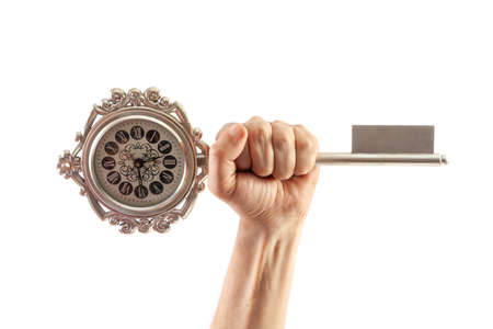 Round clock in the form of a souvenir key is held by the left hand on a white background