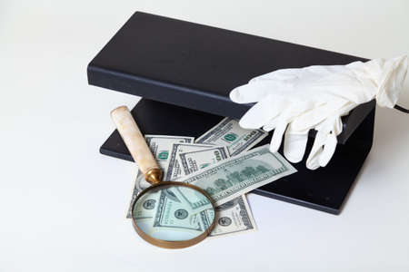Verification of dollar bills using a close-up UV detector. Nearby lies a magnifying glass on a bone handle and rubber gloves