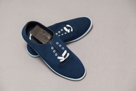 Two new blue sneakers with white soles and laces stand on a white isolated background. Zdjęcie Seryjne