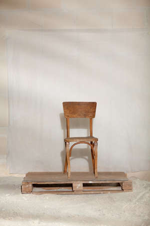 antique wooden chair stands on a wooden pallet on a white background. The pallet lies on the sand. A clear shadow is visible behind