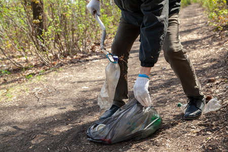 Protecting the forest from plastic waste. Activist in white gloves picks up dirty plastic dishes with a stick