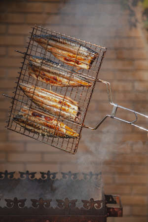 Grilled fish. Mackerel in a steel lattice turns over a brazier