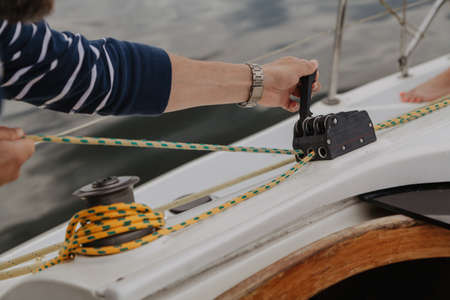 Yacht control. The captain's hands pull the rope