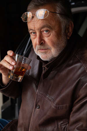 old man with a gray beard in a leather jacket holds in his hand a glass with whiskey
